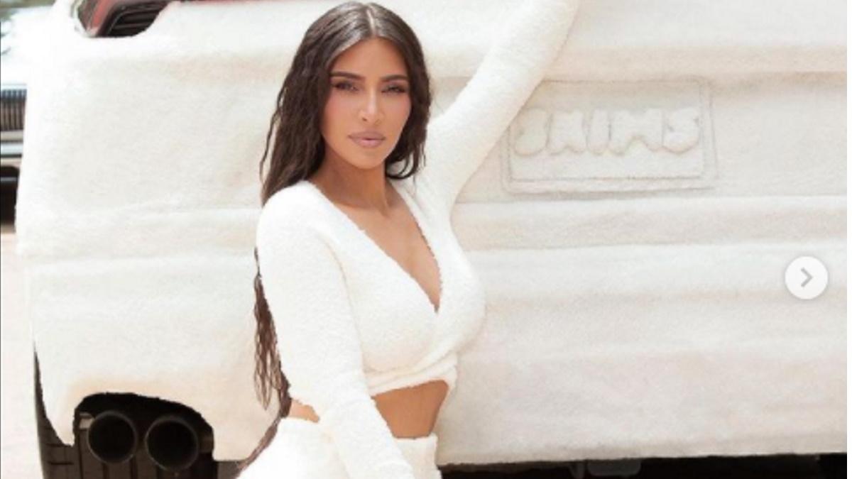 Kim Kardashian agachada em frente a um carro