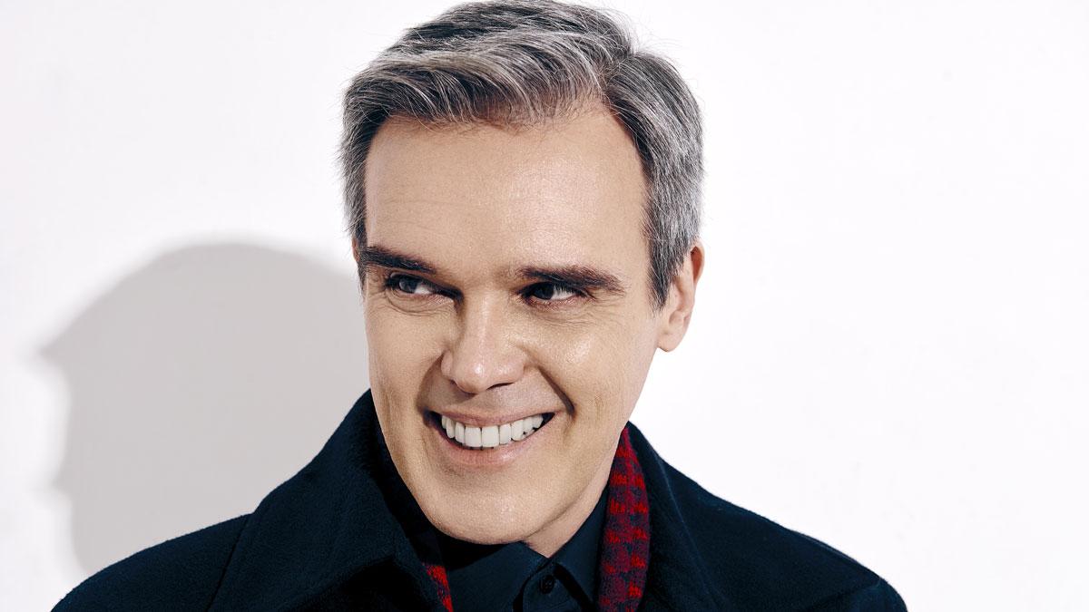 Dalton Vigh sorrindo em foto de ensaio com o fundo branco