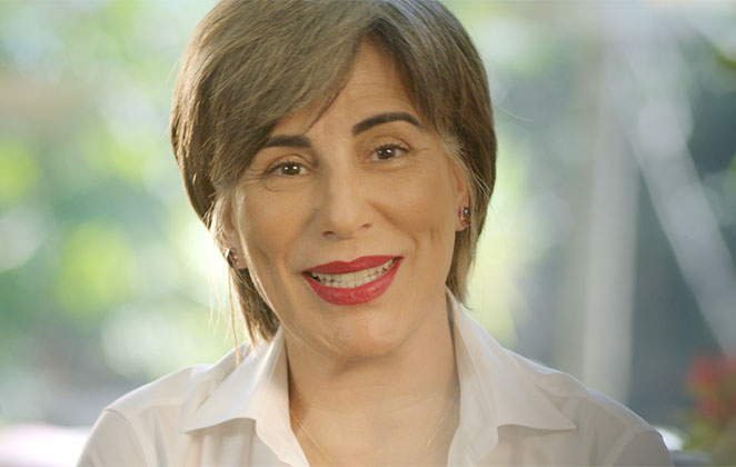 Gloria Pires esboça bonito sorriso usando batom vermelho