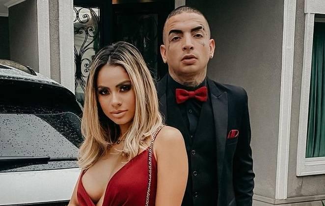 lexa de vestido vermelho e mc guimê de terno preto e gravata borboleta vermelha posando na frente de casa