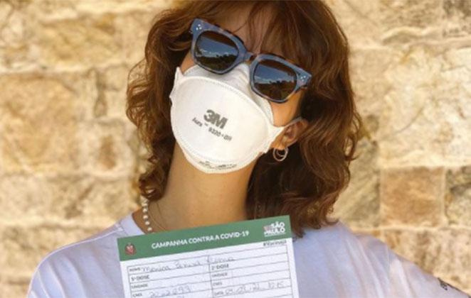 Monica Benini usando óculos de sol e mostrando cartão de vacinação