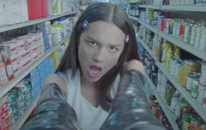 cena do clipe de good 4 com olivia rodrigo de luvas e roupa de líder de torcida interagindo om câmera do supermercado