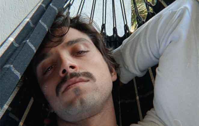 Rodrigo Simas de bigodinho, deitado na rede