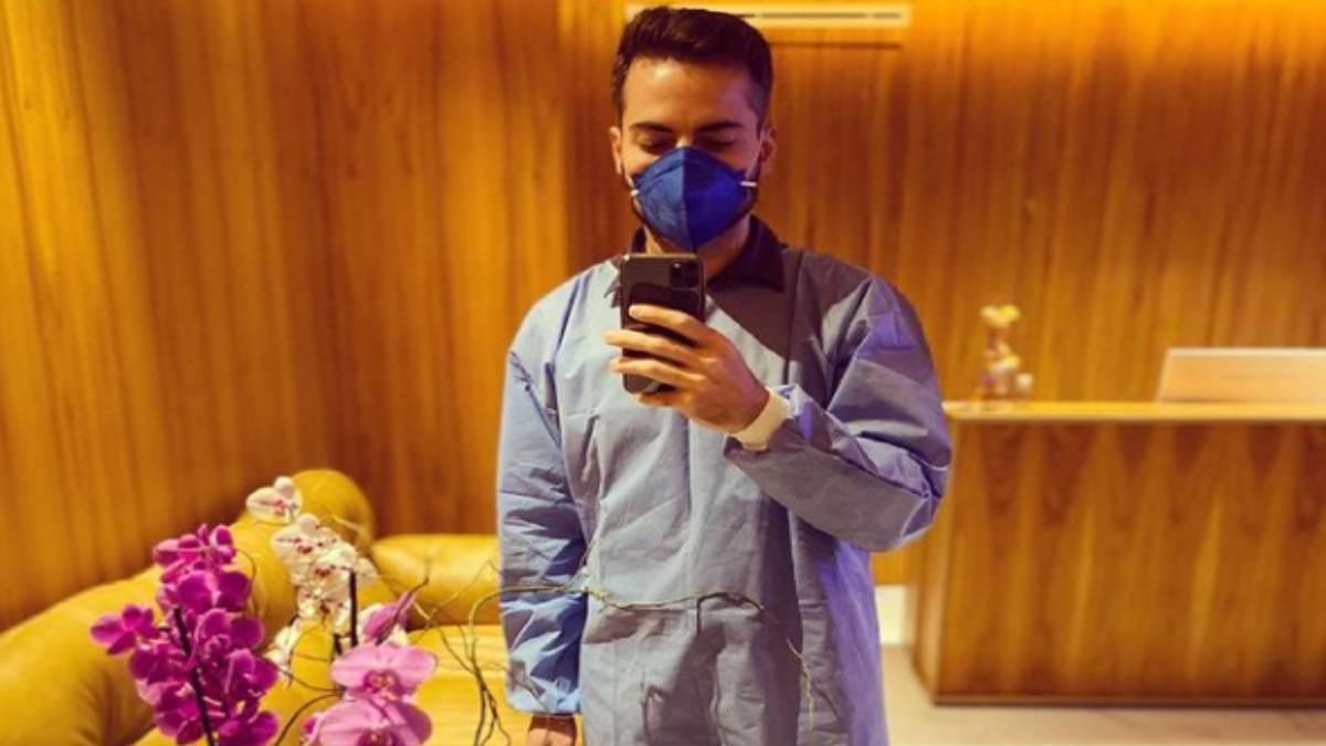 thales bretas tira foto de seu retorno ao trabalho, de jaleco em frente ao espelho