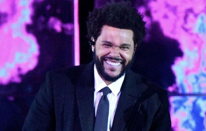 The Weeknd sorrindo com o fundo rosa e preto